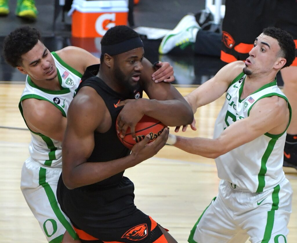Mar 12, 2021; Las Vegas, NV, USA; Oregon State Beavers forward Rodrigue Andela (34) protects the ball from Oregon Ducks guard Will Richardson (0) and Oregon Ducks guard Chris Duarte (5) during the second half at T-Mobile Arena. Mandatory Credit: Stephen R. Sylvanie-USA TODAY Sports
