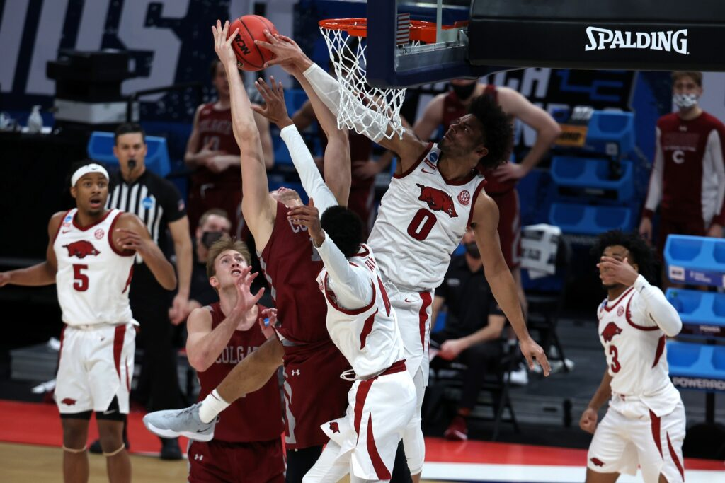 Mar 19, 2021; Indianapolis, Indiana, USA; Arkansas Razorbacks forward Justin Smith (0) blocks a shot by Colgate Raiders forward Keegan Records (14) during the second half in the first round of the 2021 NCAA Tournament at Bankers Life Fieldhouse. Mandatory Credit: Trevor Ruszkowski-USA TODAY Sports