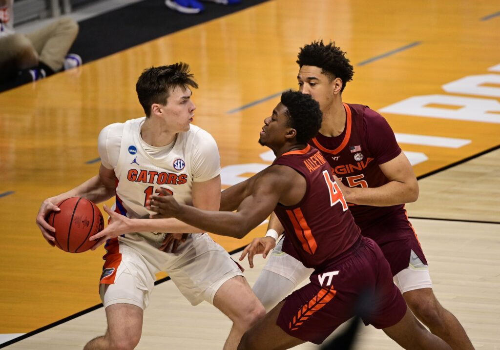 Mar 19, 2021; Indianapolis, Indiana, USA; Florida Gators forward Colin Castleton (12) is defendd by Virginia Tech Hokies guard Nahiem Alleyne (4) during the first round of the 2021 NCAA Tournament at Hinkle Fieldhouse. Mandatory Credit: Marc Lebryk-USA TODAY Sports