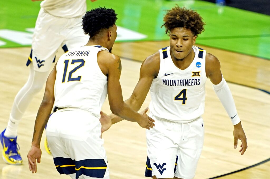 Mar 19, 2021; Indianapolis, Indiana, USA; West Virginia Mountaineers guard Miles McBride (4) celebrates with guard Taz Sherman (12) after a play during the second half against the Morehead State Eagles in the first round of the 2021 NCAA Tournament at Lucas Oil Stadium. Mandatory Credit: Andrew Nelles-USA TODAY Sports