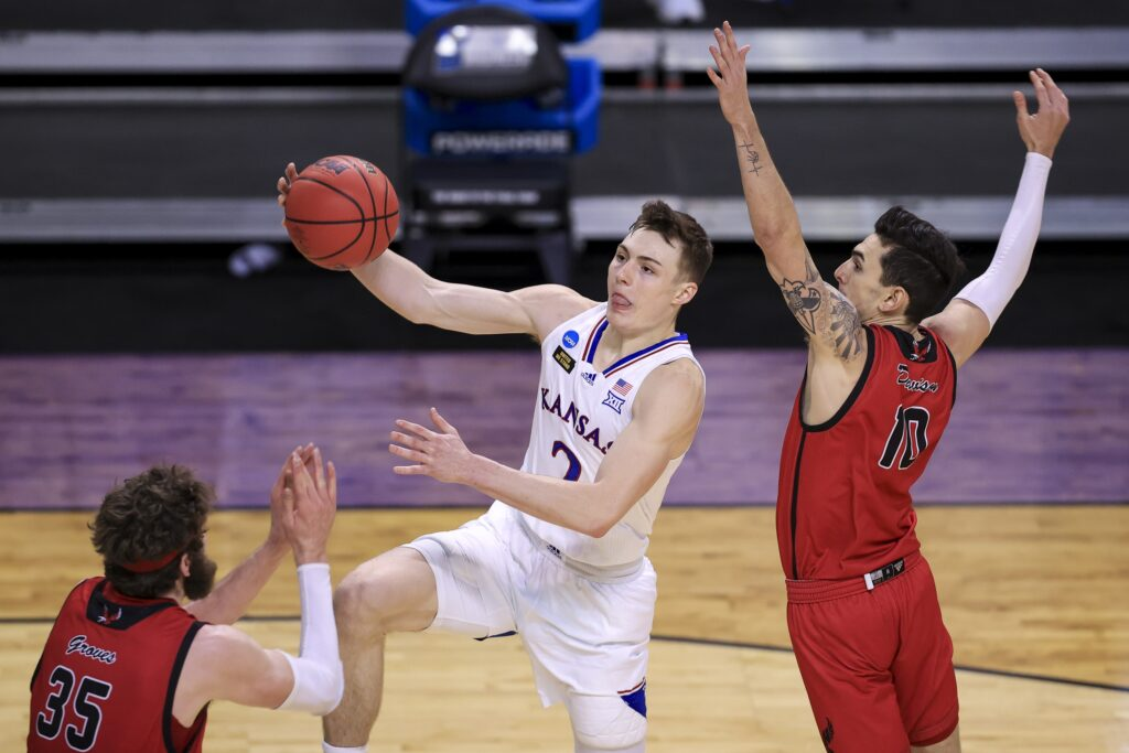 Mar 20, 2021; Indianapolis, IN, USA; Kansas Jayhawks guard Christian Braun (2) drives to the basket past Eastern Washington Eagles guard Jacob Davison (10) and forward Tanner Groves (35) during the first round of the 2021 NCAA Tournament at Indiana Farmers Coliseum.  Mandatory Credit: Aaron Doster-USA TODAY Sports