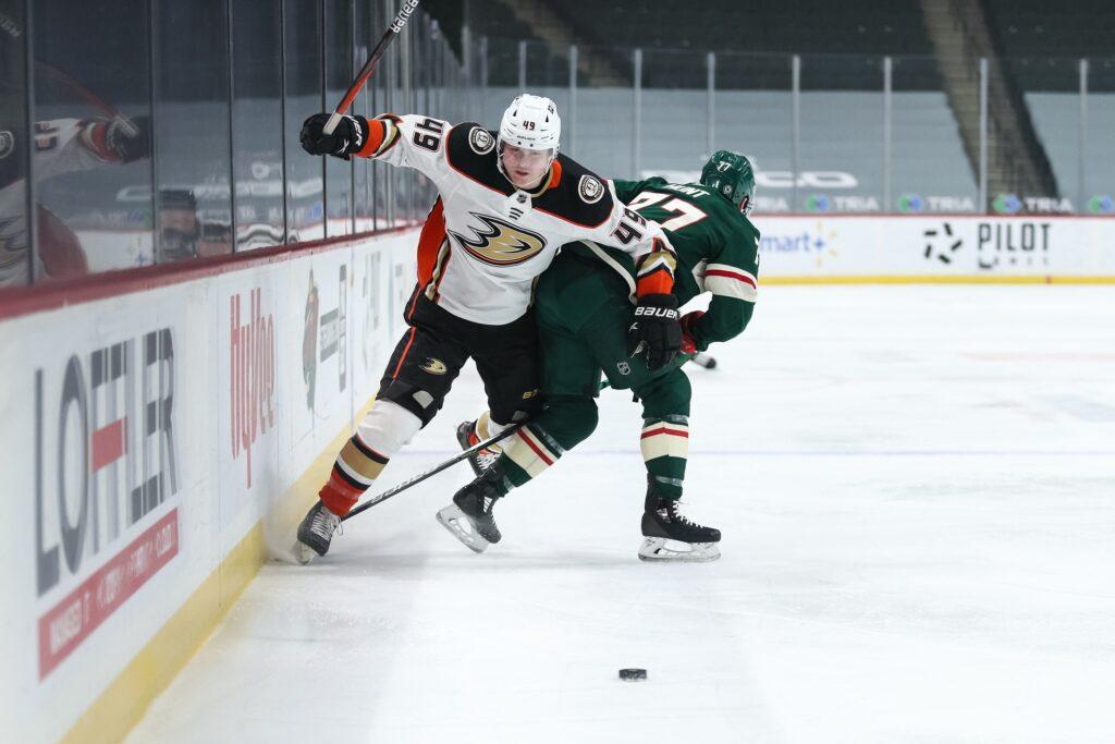 Mar 22, 2021; Saint Paul, Minnesota, USA; Minnesota Wild defenseman Brad Hunt (77) checks Anaheim Ducks left wing Max Jones (49) in the first period at Xcel Energy Center. Mandatory Credit: David Berding-USA TODAY Sports
