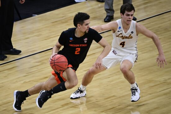 Mar 27, 2021; Indianapolis, IN, USA; Oregon State Beavers guard Jarod Lucas (2) brings the ball up court against Loyola-Chicago Ramblers guard Braden Norris (4) in the second half during the Sweet 16 of the 2021 NCAA Tournament at Bankers Life Fieldhouse.  Mandatory Credit: Marc Lebryk-USA TODAY Sports