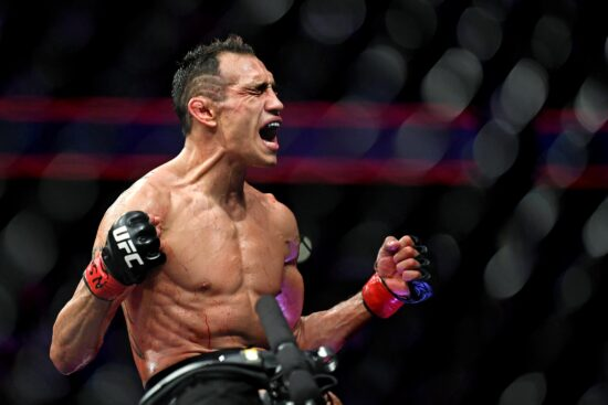 Oct 6, 2018; Las Vegas, NV, USA; Tony Ferguson (red gloves) celebrates after beating Anthony Pettis (blue gloves) during UFC 229 at T-Mobile Arena. Mandatory Credit: Stephen R. Sylvanie-USA TODAY Sports