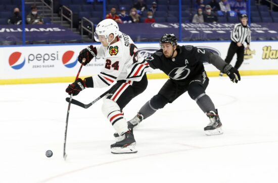 Mar 20, 2021; Tampa, Florida, USA; Chicago Blackhawks center Pius Suter (24) shoots as Tampa Bay Lightning defenseman Ryan McDonagh (27) defends during the second period at Amalie Arena. Mandatory Credit: Kim Klement-USA TODAY Sports