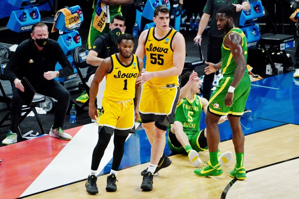 Mar 22, 2021; Indianapolis, Indiana, USA; Iowa Hawkeyes center Luka Garza (55) guides guard Joe Toussaint (1) away from Oregon Ducks guard Chris Duarte (5) as he is helped up by forward Eugene Omoruyi (2) during the first half in the second round of the 2021 NCAA Tournament at Bankers Life Fieldhouse. Mandatory Credit: Kirby Lee-USA TODAY Sports