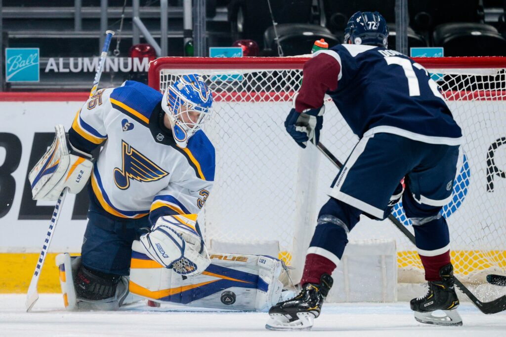 Apr 3, 2021; Denver, Colorado, USA; St. Louis Blues goaltender Ville Husso (35) makes a save ahead of Colorado Avalanche right wing Joonas Donskoi (72) in the first period at Ball Arena. Mandatory Credit: Isaiah J. Downing-USA TODAY Sports