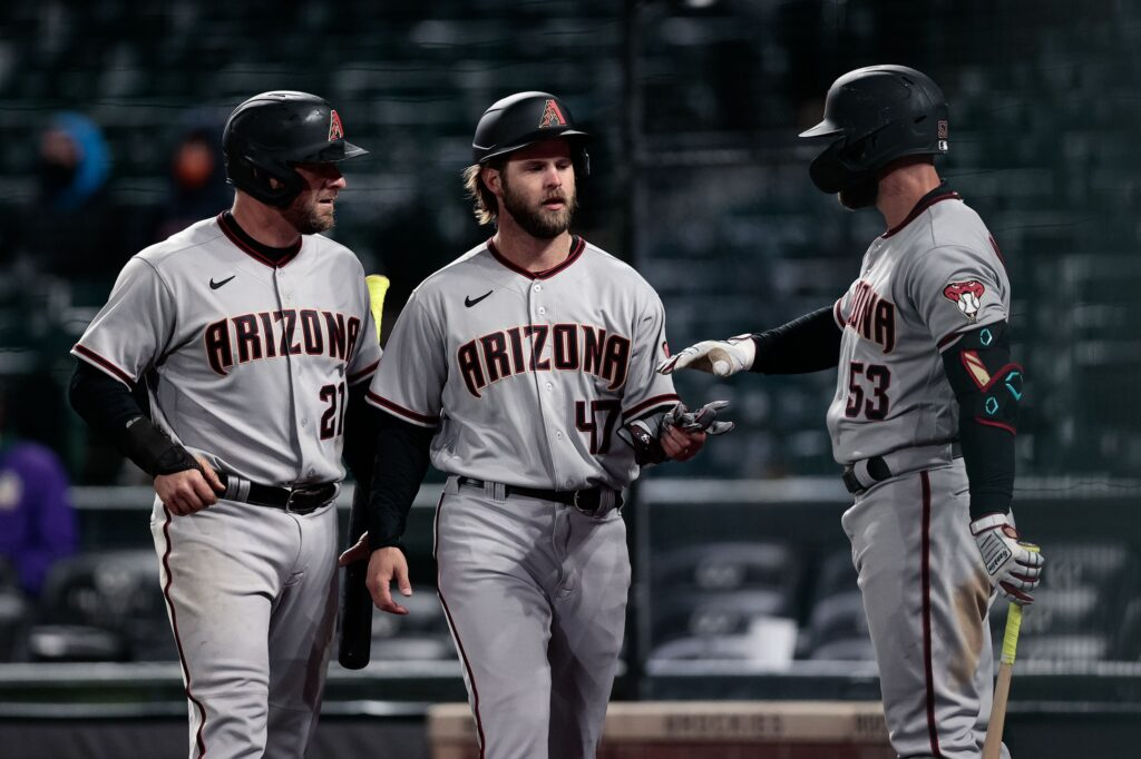 Apr 6, 2021; Denver, Colorado, USA; Arizona Diamondbacks relief pitcher Matt Peacock (47) celebrates with catcher Stephen Vogt (21) and first baseman Christian Walker (53) after scoring in the thirteenth inning against the Colorado Rockies at Coors Field. Mandatory Credit: Isaiah J. Downing-USA TODAY Sports