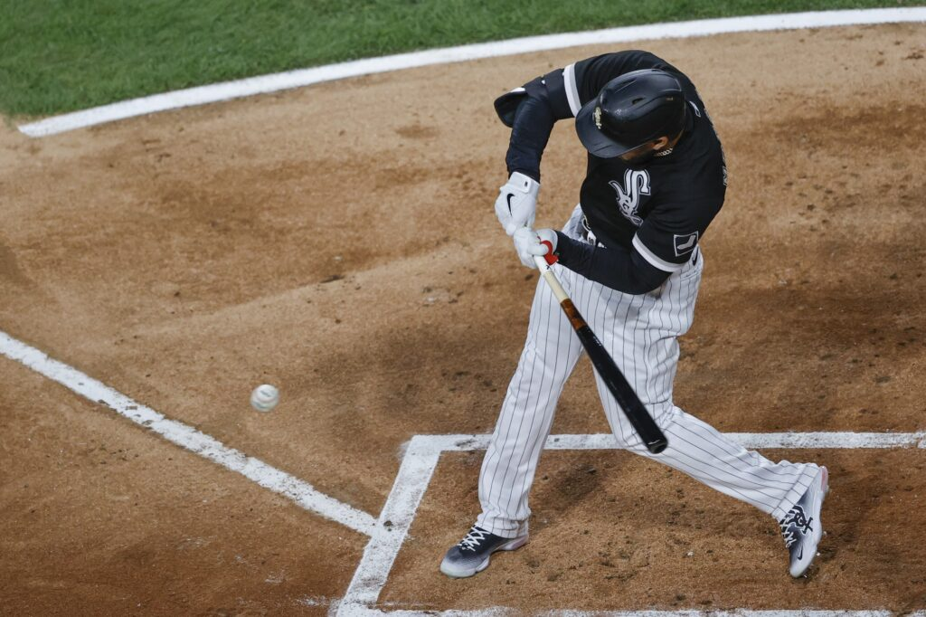 Apr 14, 2021; Chicago, Illinois, USA; Chicago White Sox third baseman Yoan Moncada (10) hits an RBI-single against the Cleveland Indians during the first inning at Guaranteed Rate Field. Mandatory Credit: Kamil Krzaczynski-USA TODAY Sports