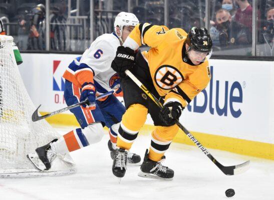 Apr 15, 2021; Boston, Massachusetts, USA; Boston Bruins left wing Jake DeBrusk (74) tries to gain control of the puck in front of New York Islanders defenseman Ryan Pulock (6) during the second period at TD Garden. Mandatory Credit: Bob DeChiara-USA TODAY Sports