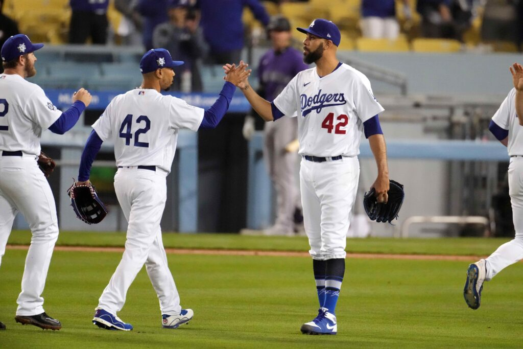 Apr 15, 2021; Los Angeles, California, USA; Los Angeles Dodgers pitcher David Price (right) is congratulated by right fielder Mookie Betts (center) and second baseman Max Muncy after the game against the Colorado Rockies at Dodger Stadium. The Dodgers defeated the Rockies 7-5.  Mandatory Credit: Kirby Lee-USA TODAY Sports