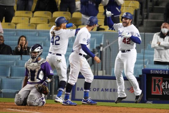 Apr 15, 2021; Los Angeles, California, USA; Los Angeles Dodgers second baseman Max Muncy (right) celebrates with shortstop Chris Taylor (center) and third baseman Justin Turner (left) after hitting a three-run home run in the seventh inning against the Colorado Rockies at Dodger Stadium. The Dodgers defeated the Rockies 7-5.  Mandatory Credit: Kirby Lee-USA TODAY Sports