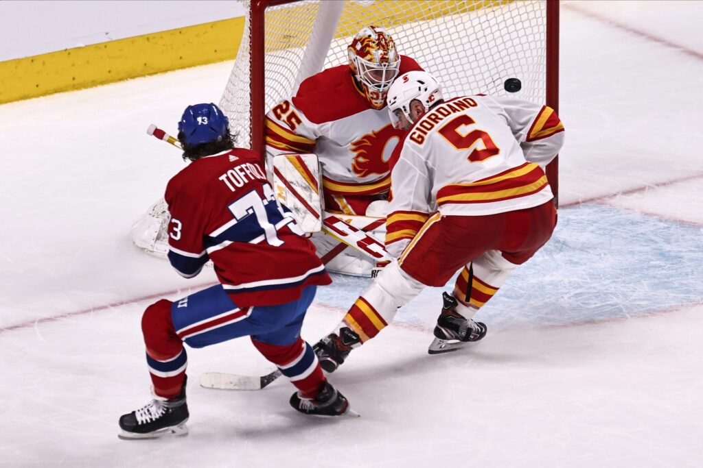 Apr 16, 2021; Montreal, Quebec, CAN; Montreal Canadiens right wing Tyler Toffoli (73) scores a goal against Calgary Flames goaltender Jacob Markstrom (25) as defenseman Mark Giordano (5) defends during the third period at Bell Centre. Mandatory Credit: Jean-Yves Ahern-USA TODAY Sports