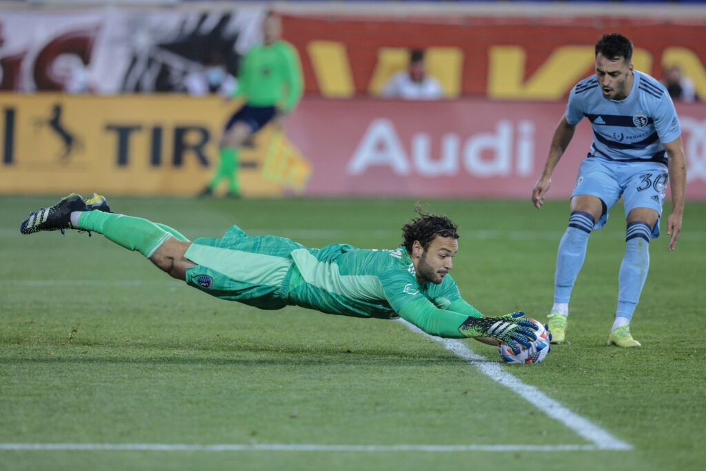 Apr 17, 2021; Harrison, New Jersey, USA; Sporting Kansas City goalkeeper John Pulskamp (1) dives for the ball in front of defender Luis Martins (36) against the New York Red Bulls during the second half at Red Bull Arena. Mandatory Credit: Vincent Carchietta-USA TODAY Sports