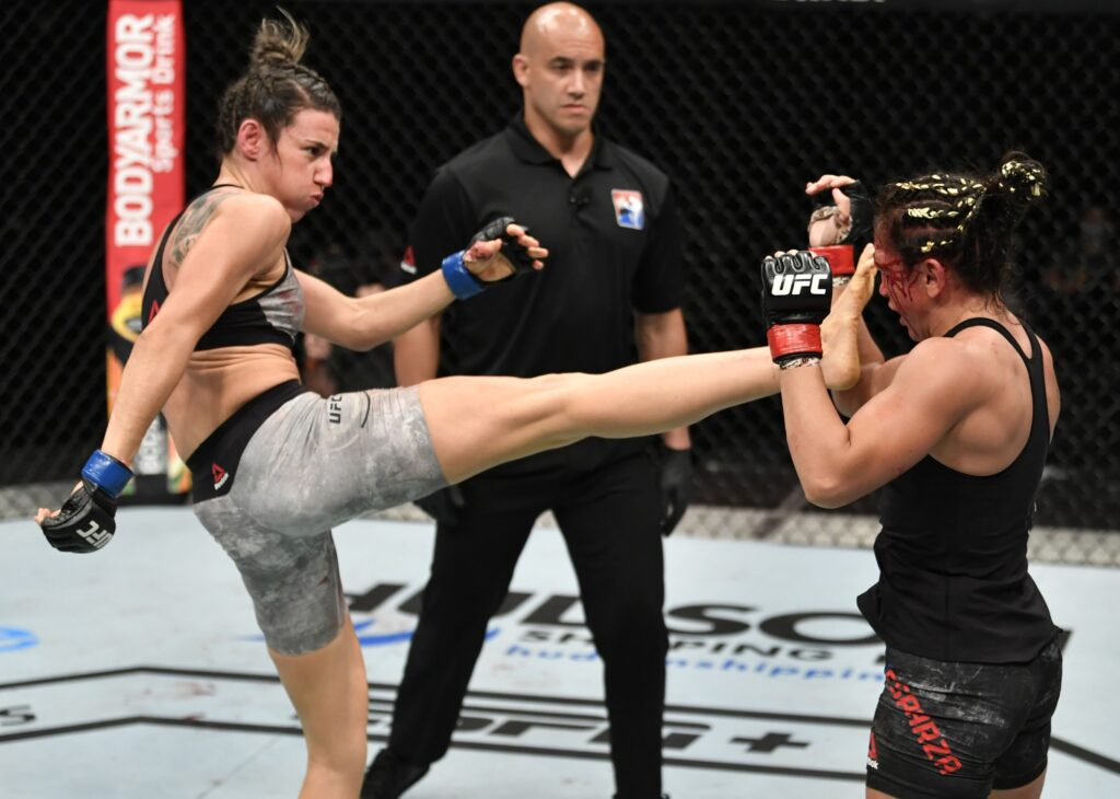 July 26, 2020; Abu Dhabi, UAE; Marina Rodriguez (blue gloves) of Brazil kicks Carla Esparza (red gloves) in their strawweight fight during the UFC Fight Night event inside Flash Forum on UFC Fight Island. Mandatory Credit: Jeff Bottari/Zuffa LLC via USA TODAY Sports