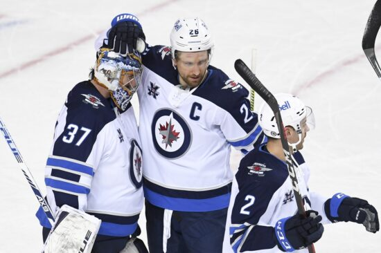 Winnipeg Jets goalie Connor Hellebuyck (37) celebrates with forward Blake Wheeler (26) after a victory over the Calgary Flames