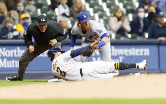Apr 30, 2021; Milwaukee, Wisconsin, USA;  Milwaukee Brewers shortstop Luis Ur'as (2) is tagged out by Los Angeles Dodgers third baseman Justin Turner (10) during the second inning at American Family Field. Mandatory Credit: Jeff Hanisch-USA TODAY Sports