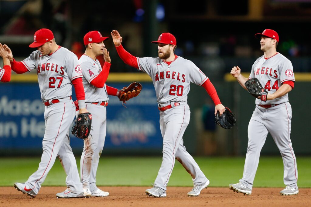 May 1, 2021; Seattle, Washington, USA; Los Angeles Angels center fielder Mike Trout (27) and right fielder Jared Walsh (20) high-five teammates after a win against the Seattle Mariners at T-Mobile Park. Mandatory Credit: Jennifer Buchanan-USA TODAY Sports