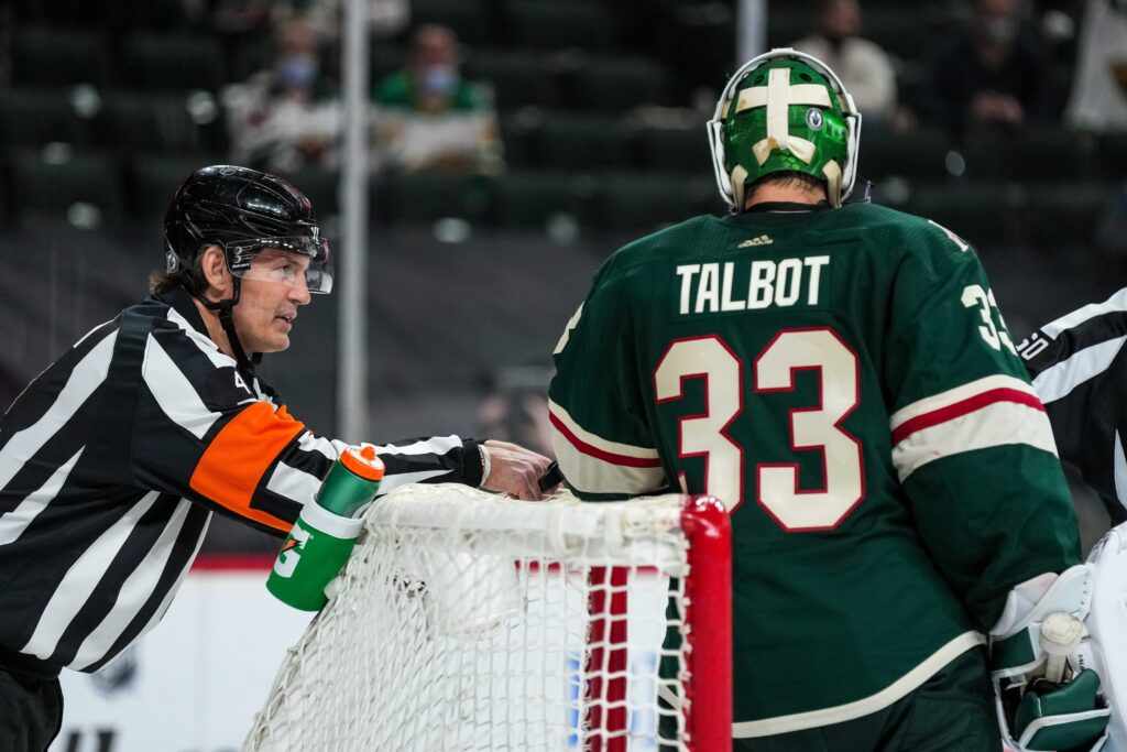 May 20, 2021; Saint Paul, Minnesota, USA; Referee Wes McCauley (left) talks to Minnesota Wild goalie Cam Talbot (33) during the third period in game three of the first round of the 2021 Stanley Cup Playoffs against the Vegas Golden Knights at Xcel Energy Center. Mandatory Credit: Brace Hemmelgarn-USA TODAY Sports