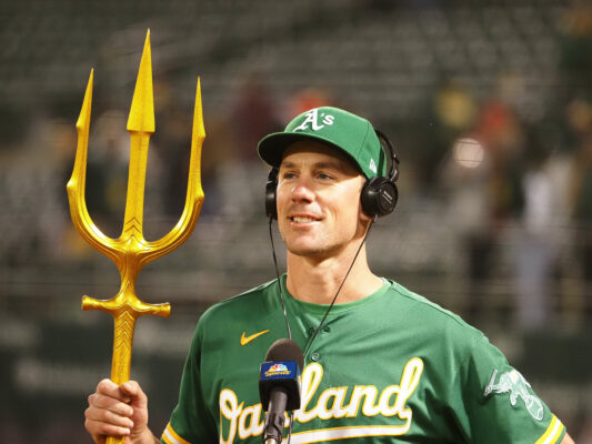 """May 27, 2021; Oakland, California, USA; Oakland Athletics starting pitcher Chris Bassitt (40) smiles with a triton for the Athletics """"ride the wave"""" motto during a post-game interview after pitching a complete game shut out against the Los Angeles Angels at RingCentral Coliseum. Mandatory Credit: Kelley L Cox-USA TODAY Sports"""