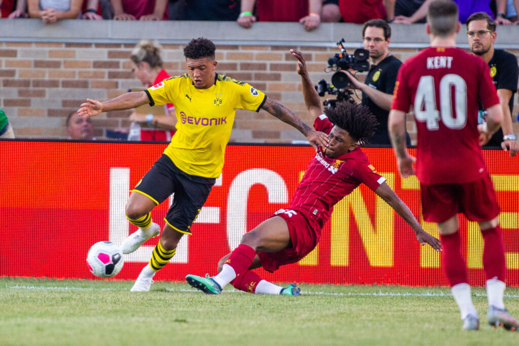 Jul 19, 2019; South Bend, IN, USA; Borussia Dortmund midfielder Jadon Sancho (7) holds off a tackle by Liverpool forward Yasser Larouci (65) in the first half of a pre-season preparation soccer match at Notre Dame. Mandatory Credit: Trevor Ruszkowski-USA TODAY Sports