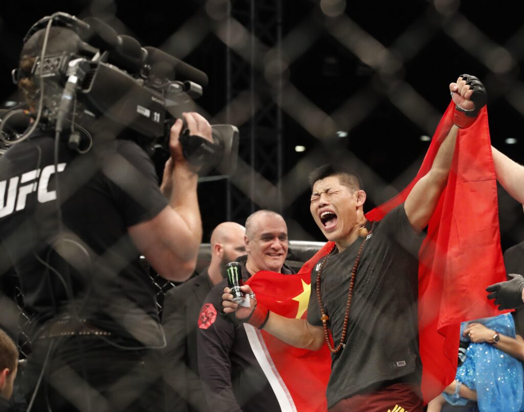 Aug 31, 2019; Shenzhen, China; Li Jingliang (red gloves) defeats Elizeu Dos Santos (blue gloves) during UFC Fight Night at Shenzhen Universiade Sports Centre. Mandatory Credit: David G. McIntyre-USA TODAY Sports