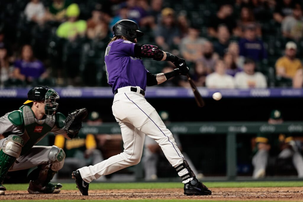 Jun 4, 2021; Denver, Colorado, USA; Colorado Rockies right fielder Charlie Blackmon (19) hits an RBI single in the seventh inning against the Oakland Athletics at Coors Field. Mandatory Credit: Isaiah J. Downing-USA TODAY Sports