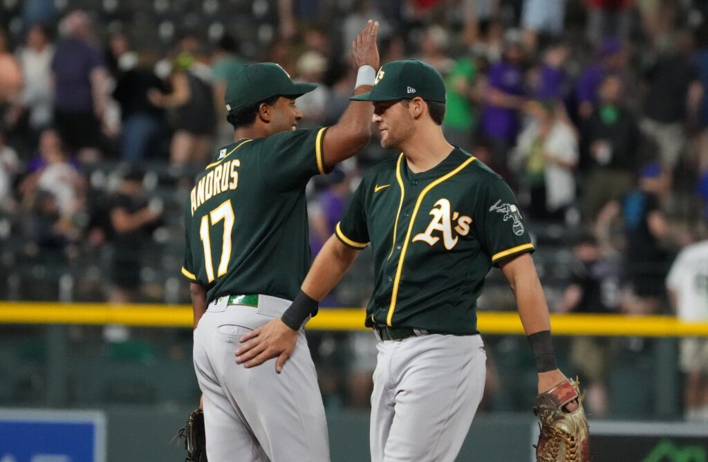Jun 5, 2021; Denver, Colorado, USA; Oakland Athletics left fielder Mark Canha (20) and shortstop Elvis Andrus (17) celebrate after defeating the Colorado Rockies at Coors Field. Mandatory Credit: Ron Chenoy-USA TODAY Sports