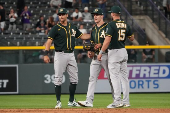 Jun 5, 2021; Denver, Colorado, USA; Oakland Athletics third baseman Chad Pinder (4) and left fielder Mark Canha (20) and left fielder Seth Brown (15) celebrate after defeating the Colorado Rockies at Coors Field. Mandatory Credit: Ron Chenoy-USA TODAY Sports