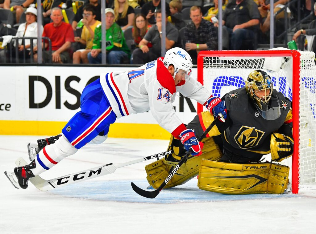 Jun 14, 2021; Las Vegas, Nevada, USA; Montreal Canadiens center Nick Suzuki (14) is tripped up by the stick of Vegas Golden Knights goaltender Marc-Andre Fleury (29) during the third period of game one of the 2021 Stanley Cup Semifinals at T-Mobile Arena. Mandatory Credit: Stephen R. Sylvanie-USA TODAY Sports