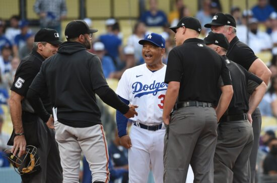 Jun 28, 2021; Los Angeles, California, USA;  Los Angeles Dodgers manager Dave Roberts (30) and San Francisco Giants manager Gabe Kepler talk with the officials before the game at Dodger Stadium. Mandatory Credit: Richard Mackson-USA TODAY Sports