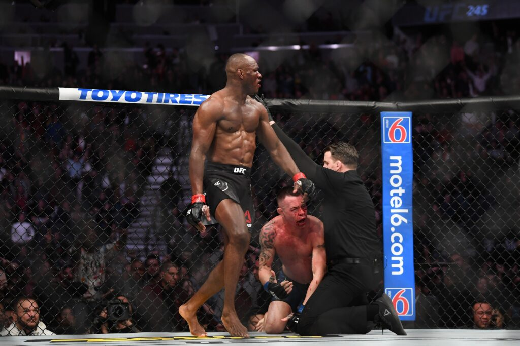 Dec 14, 2019; Las Vegas, NV, USA; (Editor's Note: Graphic Content) Kamaru Usman (red gloves) reacts as referee Marc Goddard stops his bout against Colby Covington (blue gloves) during UFC 245 at T-Mobile Arena. Mandatory Credit: Stephen R. Sylvanie-USA TODAY Sports