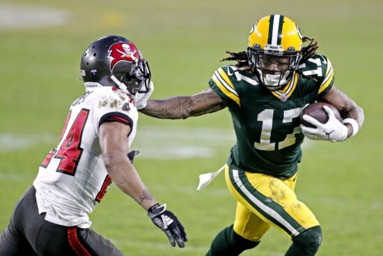 Jan 24, 2021; Green Bay, Wisconsin, USA; Green Bay Packers wide receiver Davante Adams (17) runs the ball against Tampa Bay Buccaneers cornerback Carlton Davis (24) during the fourth quarter in the NFC Championship Game at Lambeau Field. Mandatory Credit: Jeff Hanisch-USA TODAY Sports