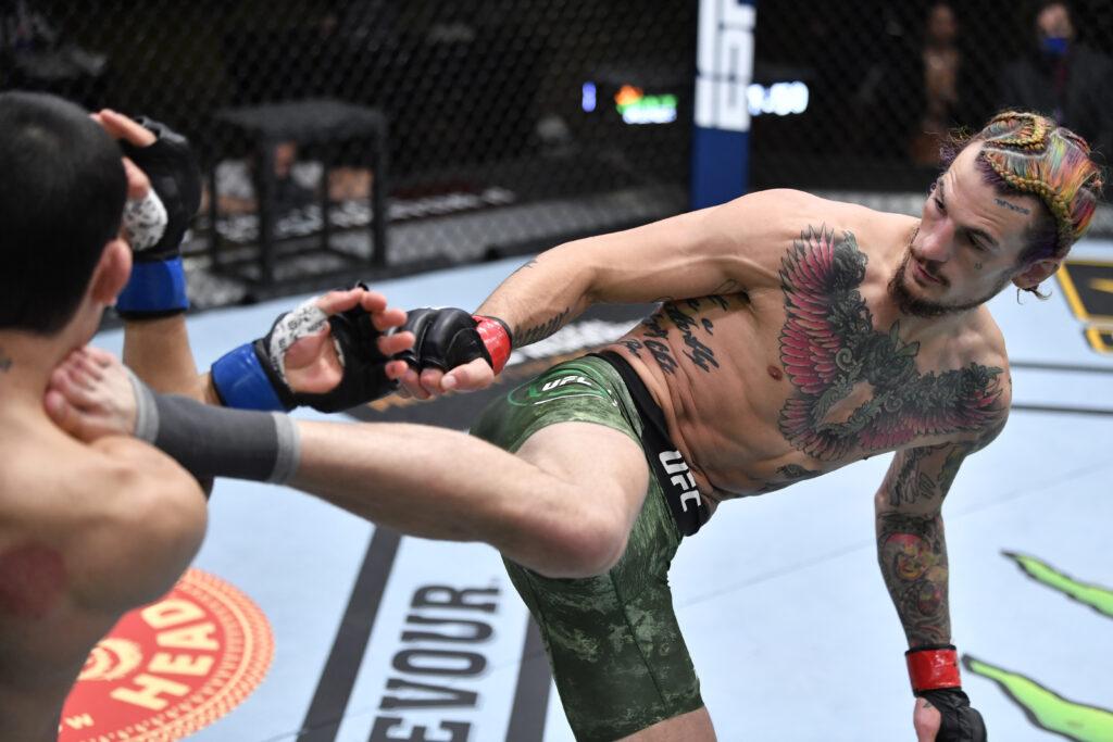 Mar 27, 2021; Las Vegas, NV, USA;  Sean O'Malley kicks Thomas Almeida of Brazil in their bantamweight fight during the UFC 260 event at UFC APEX on March 27, 2021 in Las Vegas, Nevada.  Mandatory Credit: Jeff Bottari/Handout Photo via USA TODAY Sports