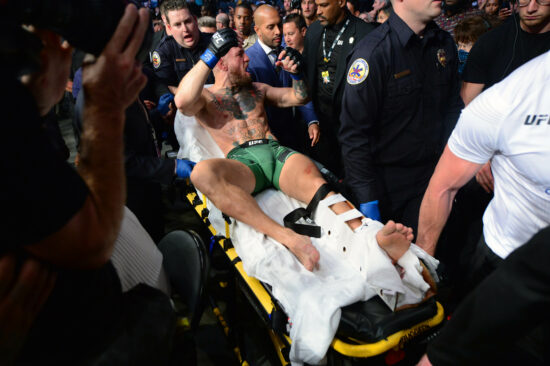 Jul 10, 2021; Las Vegas, Nevada, USA; Conor McGregor is carried off on a stretcher following an injury in his loss against Dustin Poirier during UFC 264 at T-Mobile Arena. Mandatory Credit: Gary A. Vasquez-USA TODAY Sports