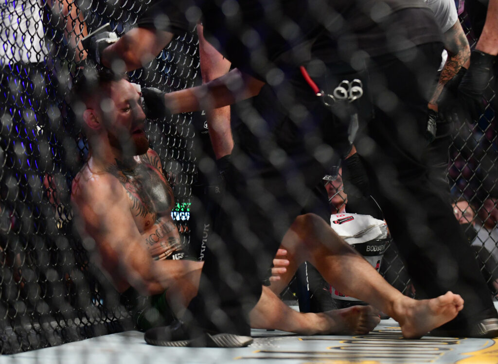 Jul 10, 2021; Las Vegas, Nevada, USA; Conor McGregor is looked at by the fight doctor followin an injury against Dustin Poirier during UFC 264 at T-Mobile Arena. Mandatory Credit: Gary A. Vasquez-USA TODAY Sports
