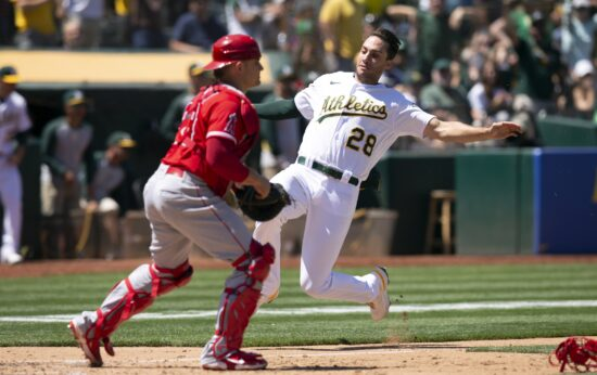 Jul 20, 2021; Oakland, California, USA; Oakland Athletics first baseman Matt Olson (28) slides home past Los Angels catch Max Stassi (33) during the sixth inning at RingCentral Coliseum. Mandatory Credit: D. Ross Cameron-USA TODAY Sports