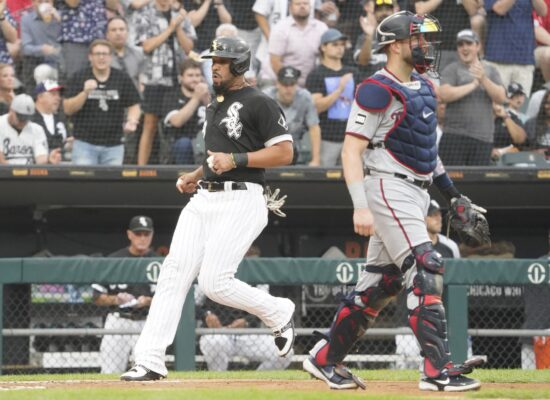 Jul 20, 2021; Chicago, Illinois, USA; Chicago White Sox first baseman Jose Abreu (79) scores as Minnesota Twins catcher Mitch Garver (8) stands nearby during the first inning at Guaranteed Rate Field. Mandatory Credit: David Banks-USA TODAY Sports