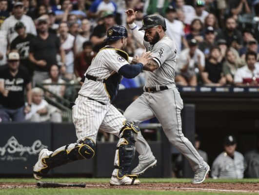 Jul 24, 2021; Milwaukee, Wisconsin, USA; Chicago White Sox third baseman Yoan Moncada (10) was ruled out after failing to touch home plate trying to score in the fifth inning as Milwaukee Brewers catcher Manny Pina (9) reaches for the ball at American Family Field. Mandatory Credit: Benny Sieu-USA TODAY Sports