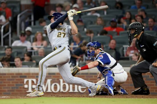Jul 30, 2021; Atlanta, Georgia, USA; Milwaukee Brewers shortstop Willy Adames (27) hits a two-run home run as Atlanta Braves catcher Stephen Vogt (26) is shown on the play during the fourth inning at Truist Park. Mandatory Credit: Jason Getz-USA TODAY Sports