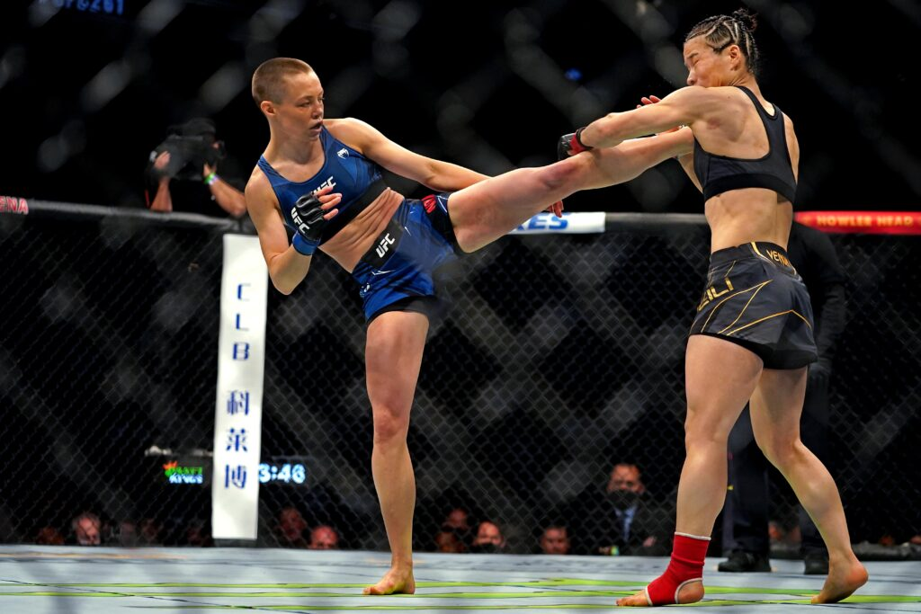 Apr 24, 2021; Jacksonville, Florida, USA; Rose Namajunas (Blue Gloves) kicks Zhang Weili (Red Gloves) for a TKO during UFC 261 at VyStar Veterans Memorial Arena. Mandatory Credit: Jasen Vinlove-USA TODAY Sports