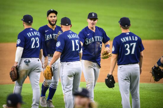 Aug 19, 2021; Arlington, Texas, USA; Seattle Mariners right fielder Jake Bauers (5) and first baseman Ty France (23) and third baseman Kyle Seager (15) and relief pitcher Paul Sewald (37) celebrate the win over the Texas Rangers at Globe Life Field. Mandatory Credit: Jerome Miron-USA TODAY Sports