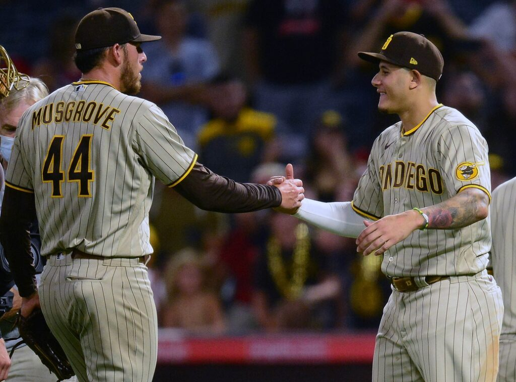Aug 27, 2021; Anaheim, California, USA; San Diego Padres starting pitcher Joe Musgrove (44) and designated hitter Manny Machado (13) celebrate the 5-0 victory against the Los Angeles Angels at Angel Stadium. Mandatory Credit: Gary A. Vasquez-USA TODAY Sports