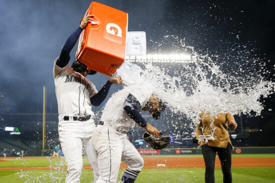 Aug 31, 2021; Seattle, Washington, USA; Seattle Mariners second baseman Abraham Toro (13) is doused with ice water by catcher Luis Torrens (22) during a postgame interview following a 4-0 victory against the Houston Astros at T-Mobile Park. Mandatory Credit: Joe Nicholson-USA TODAY Sports