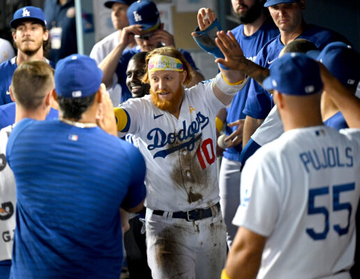 Sep 1, 2021; Los Angeles, California, USA; Los Angeles Dodgers third baseman Justin Turner (10) gets high fives in the dugout after scoring a run in the eighth inning against the Atlanta Braves at Dodger Stadium. Mandatory Credit: Jayne Kamin-Oncea-USA TODAY Sports