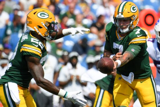 Aug 28, 2021; Orchard Park, New York, USA; Green Bay Packers quarterback Kurt Benkert (7) hands the ball off to running back Dexter Williams (22) against the Buffalo Bills during the second half at Highmark Stadium. Mandatory Credit: Rich Barnes-USA TODAY Sports