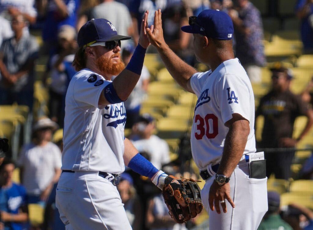 Sep 12, 2021; Los Angeles, California, USA; Los Angeles Dodgers third baseman Justin Turner (10) high-fives manager Dave Roberts after the Dodgers beat the San Diego Padres 8-0 at Dodger Stadium. Mandatory Credit: Robert Hanashiro-USA TODAY Sports
