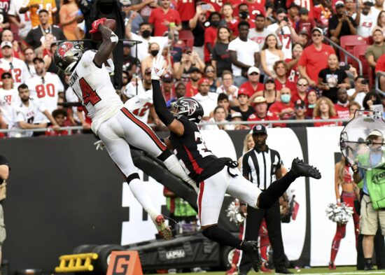 Sep 19, 2021; Tampa, Florida, USA; Tampa Bay Buccaneers wide receiver Chris Godwin (14) catches a touchdown pass over Atlanta Falcons defensive back Isaiah Oliver (26) in the second half  at Raymond James Stadium. Mandatory Credit: Jonathan Dyer-USA TODAY Sports