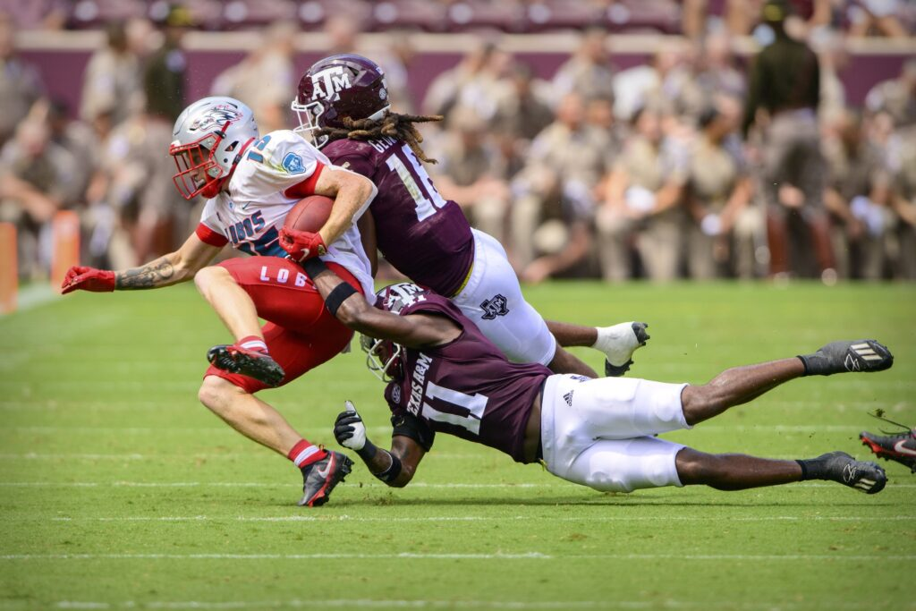 Sep 18, 2021; College Station, Texas, USA; New Mexico Lobos wide receiver Luke Wysong (15) and Texas A&M Aggies defensive back Deuce Harmon (11) and defensive back Brian George (16) in action during the game between the Texas A&M Aggies and the New Mexico Lobos at Kyle Field. Mandatory Credit: Jerome Miron-USA TODAY Sports