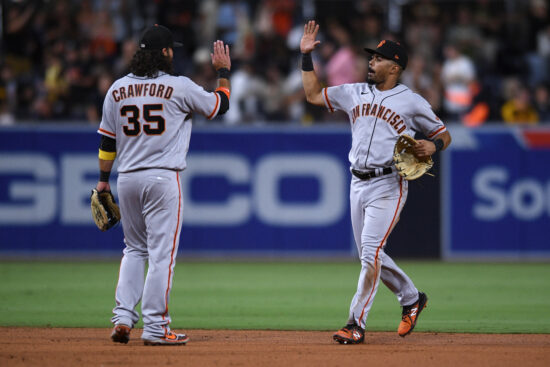 Sep 21, 2021; San Diego, California, USA; San Francisco Giants shortstop Brandon Crawford (35) and right fielder LaMonte Wade (right) celebrate on the field after defeating the San Diego Padres at Petco Park. Mandatory Credit: Orlando Ramirez-USA TODAY Sports